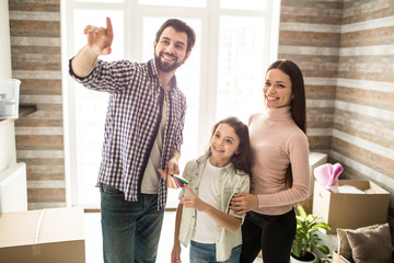 Beautiful family is standing together in their new apartment. Man is looking straight and pointing. His wife and daughter are looking to the same side and smiling. They look happy together.