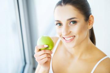 Woman Eating Apple. Beautiful Girl With White Teeth Biting Apple. High Resolution Image