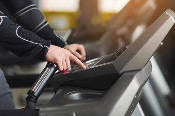 Unrecognizable man in gym running on treadmill