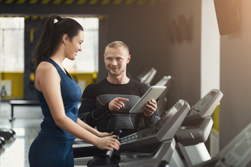 Fitness coach helps woman on elliptical trainer