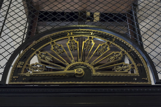 turn of the century elevator . close up on elevator's floor indicator. The elevator itself is iron painted black, the numbers and indicator are bronze