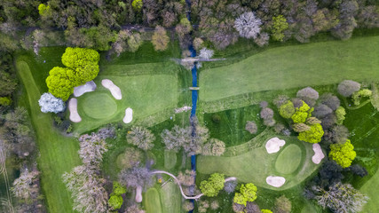 Drone view of a golf course with a small river