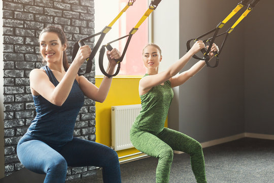 Women performing TRX suspension training in gym