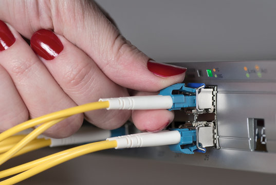 Female engineer connecting fiber optic patchcord to the data switch.
