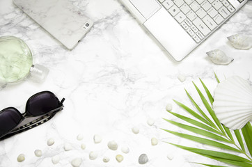 Women's fashion accessories, computer, phone, palm leaf on marble background