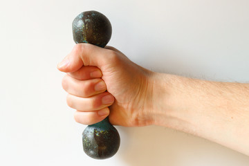 The hand holds the dumbbell on a white background