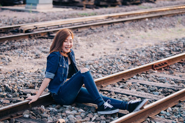 Portrait of beautiful asian woman  in A white Jean style on the railway vintage style,Thailand people,Hipster girl wear denims dress pose for take a picture