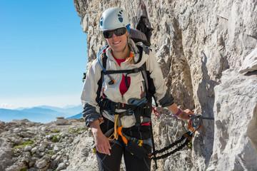 Happy female mountaineer climbing via ferrata.