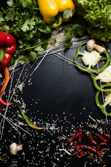 natural organic vegetable peppers and noodles on dark background. food ingredients. meal preparation. free space concept