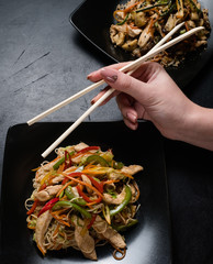 asian restaurant cuisine serving. woman eating chicken and vegetable salad with chopsticks. oriental food culture