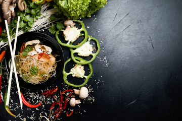 oriental cuisine food. traditional meal. noodle and meat soup in a bowl with vegetables on dark background. free space concept