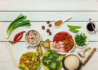 Chinese food background, raw ingredients, meat, vegetables, rice, beans, nuts and spicies on old light blue wooden table. Healthy food, clean eatind and diet concept, Top view, overhead, flat lay