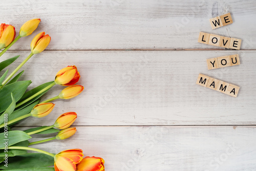 Yellow and red tulips on whitewashed wood with Mother's Day message