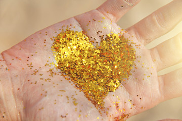 A golden shining heart lies in the hands of the girl. Heart in the palms. Golden heart