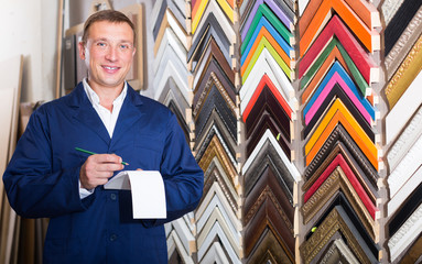 attractive man seller in picture framing studio with wooden details