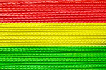 Red yellow & green tricolor flag. Metal reinforcement bars w/ periodic profile texture. New iron rod w/o rust, steel construction armature pile. Rasta strength concept. Copy space, close up background