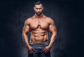 Portrait of a shirtless tall huge male with a muscular body with a stylish haircut and beard, in a sports shorts, posing in a studio.