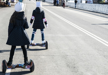 Two girls ride a two-wheeled Hoverboard. Copy space.