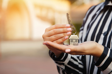 Key to new home in hand on house background