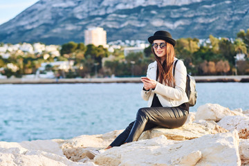 Pretty young woman in black hat sitting on a rock with a cell phone