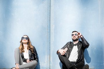 Couple sitting on the blue wall background