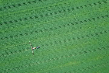 Aerial view Farm machinery spraying chemicals on the large green field, agricultural spring background.