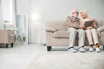 Modern technology. Nice joyful elderly couple sitting together on the sofa while using a tablet
