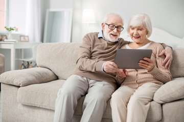 Modern device. Joyful aged people smiling while looking at the tablet screen