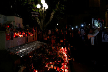 People take part in a vigil and demonstration marking six months since the assassination of anti-corruption journalist Daphne Caruana Galizia in a car bomb, at her makeshift memorial in Valletta