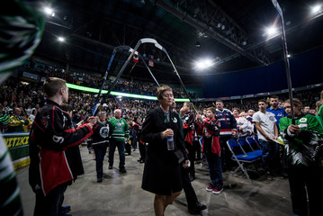 Family enter through an arch of hockey sticks at a memorial celebration for Evan Thomas, one of the players killed in the bus crash carrying the Humboldt Broncos Junior A hockey team