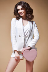 Portrait of pretty beautiful fashion sexy model business lady dark hair woman makeup care face cosmetic accessory lather bag wear office style white jacket manager boss suit jewelry luxury lifestyle.