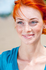 Outdoor portrait of a young beautiful redhead freckled woman smiling happily