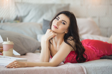 Young sportive woman is lying in bed and drinking coffee with donuts