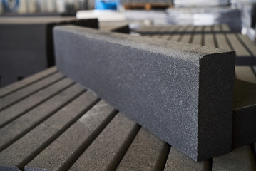 Concrete road curbs at the factory for the production of cement products, paving slabs, construction material for a new sidewalk