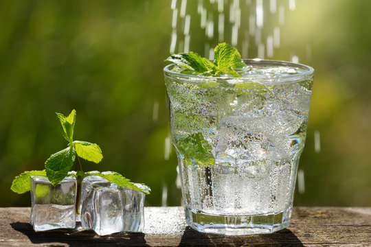 drink mojito with mint and lime in a glass in the open air, close to ice cubes, against the background of greenery, water flows