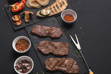 Small pork steaks on black background