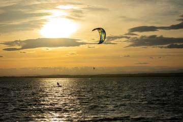 Un kitesurfer sous un coucher de soleil
