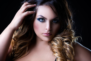 Plus size fashion model, beauty woman with professional makeup and hairstyle on black background