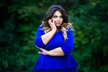 Depressed plus size fashion model in blue dress outdoors, beauty woman with professional makeup and hairstyle
