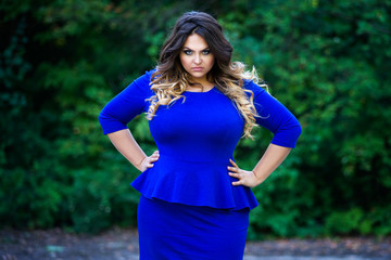 Angry plus size fashion model in blue dress outdoors, beauty woman with professional makeup and hairstyle