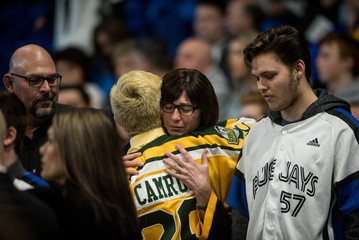 Bus crash survivor Brayden Camrud receives a hug at a memorial celebration for Evan Thomas, one of the players killed in the bus crash carrying the Humboldt Broncos Junior A hockey team