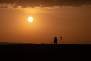 photographer with tripod at sunrise