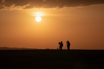 photographers with tripod at sunrise