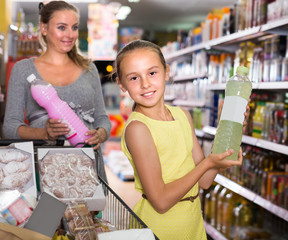 Child is showing purchases which they chosen with mother