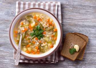 Vegan soup with pickled cucumbers and pearl barley, rassolnik. traditional homemade Russian cuisine. on a wooden table
