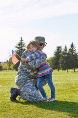 Little kid with usa flag is embracing her father. Military daddy is hugging with his little daughter on the park lawn.