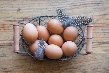 Basket of eggs and feathers on wooden background