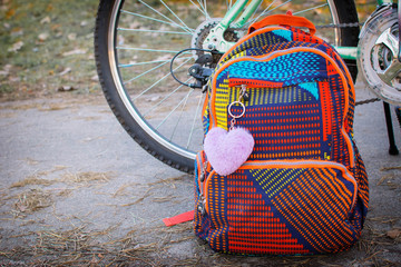 colorful backpack near a female bicycle