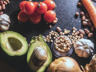 raw fresh vegan healthy fruit and vegetables on black dark surface