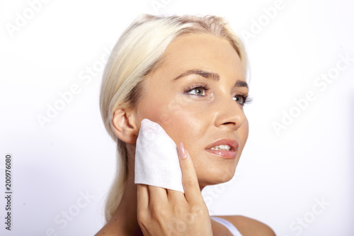 Young woman clean face with wet wipes